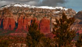 A light blanket of snow covers the distant red rock of Sedona in winter