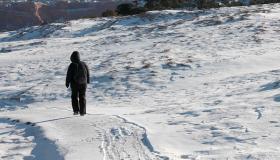 Young trekker walking on a snow trail in Arizona